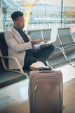 O homem de negócios novo é assentado no aeroporto que trabalha com um portátil fotografia de stock