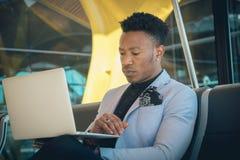 O homem de negócios novo é assentado no aeroporto que trabalha com um portátil imagens de stock royalty free