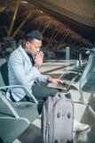 O homem de negócios novo é assentado no aeroporto que trabalha com um portátil fotos de stock royalty free