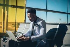 O homem de negócios novo é assentado no aeroporto que trabalha com um portátil imagem de stock