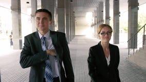 O homem de negócios novo acompanha um delegado atrativo ao prédio de escritórios video estoque