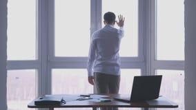 O homem de negócios novo admira a vista e os toques a janela em um escritório imagem de stock