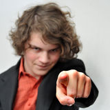 O homem de negócios novo aponta seu dedo em você foto de stock