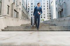 o homem de negócios novo atrativo no terno à moda com bagagem e voo tickets ir abaixo das escadas fotografia de stock royalty free