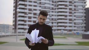 O homem de negócios novo atrativo no terno preto joga documenta para fora exterior contra o prédio de escritórios vídeos de arquivo