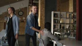 O homem de negócios novo caucasiano seguro novo em ocasional vem trabalhar em um escritório ou em um local de trabalho moderno O  filme