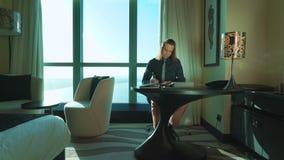 O homem de negócios novo com cabelo longo está trabalhando na tabuleta, datilografa o texto, pensa, chama-o pelo telefone celular video estoque