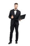 O homem de negócios novo com o portátil que mostra os polegares levanta o K gesto do sinal da mão Fotos de Stock Royalty Free