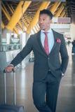 O homem de negócios novo com uma mala de viagem levanta-se fora do airpo imagens de stock royalty free
