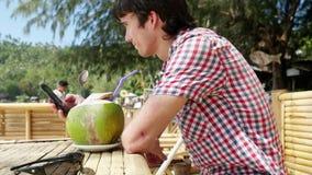 O homem de negócios novo considerável nos óculos de sol bebe o suco fresco do coco em um café da praia com opinião do mar em palm vídeos de arquivo