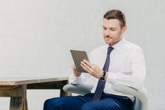 O homem de negócios novo considerável próspero olha webinar em linha no tablet pc moderno, vestido na roupa formal, senta-me na c fotografia de stock royalty free