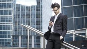 O homem de negócios novo considerável que veste vidros e um terno está estando em uma rua e está texting em um vento Fotografia de Stock