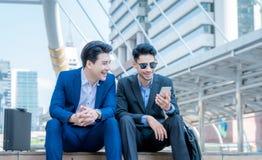 O homem de negócios novo de sorriso usa o smartphone que aprecia uma conversação positiva que fala com um sócio comercial maduro  foto de stock