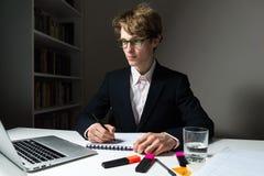 O homem de negócios novo determinado e seguro trabalha horas atrasadas no escritório no projeto encontrar o fim do prazo imagem de stock royalty free