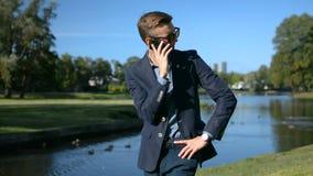 O homem de negócios novo em um terno e em óculos de sol está usando o smartphone do telefone celular que fala na frente de uma pa video estoque