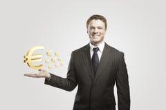 O homem de negócios novo escolhe sinais de um euro do ouro. Imagem de Stock Royalty Free