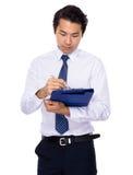 O homem de negócios novo escreve na prancheta Imagem de Stock