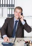 O homem de negócios novo está discando um número no telefone Fotos de Stock