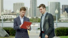 O homem de negócios novo está encontrando seu amigo em uma rua vídeos de arquivo