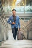 O homem de negócios novo está escalando escadas no aeroporto que fala por t imagem de stock