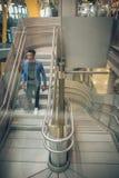 O homem de negócios novo está escalando escadas no aeroporto que fala por t fotografia de stock royalty free