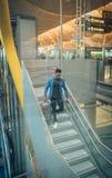 O homem de negócios novo está escalando escadas no aeroporto que fala por t imagem de stock royalty free