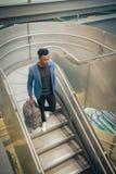 O homem de negócios novo está escalando escadas no aeroporto que fala por t foto de stock