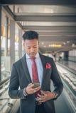 O homem de negócios novo está indo ao aeroporto que olha seu smarpho fotografia de stock