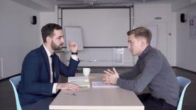 O homem de negócios novo está nas negociações com o empregado no escritório moderno filme