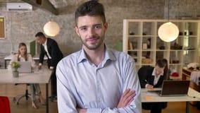 O homem de negócios novo está olhando na câmera no escritório, sorrindo, braços é cruzado, seus colegas é trabalhos em rede com filme