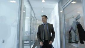 O homem de negócios novo está procurando a sala alugar no prédio de escritórios moderno e o secretário fêmea ajuda-lhe video estoque