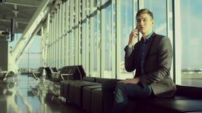 O homem de negócios novo está sentando-se no aeroporto e está falando-se sobre um smartphone video estoque
