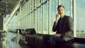 O homem de negócios novo está tendo um bate-papo sobre seu smartphone no aeroporto filme