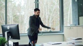 O homem de negócios novo excitado está contando o dinheiro no escritório então que joga o dinheiro no ar e que dança expressando  filme