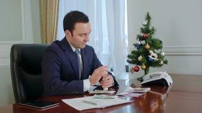 O homem de negócios novo feliz conta o salário perto da árvore do ano novo no escritório filme