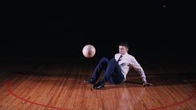 O homem de negócios novo joga o futebol do futebol no fundo preto video estoque
