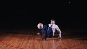 O homem de negócios novo joga o futebol do futebol no fundo preto filme