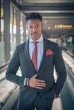 O homem de negócios novo levanta-se fora do aeroporto que olha o th fotografia de stock royalty free