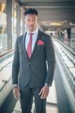 O homem de negócios novo levanta-se fora do aeroporto que olha o th imagem de stock royalty free