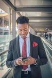 O homem de negócios novo levanta-se fora do aeroporto que olha o th fotografia de stock