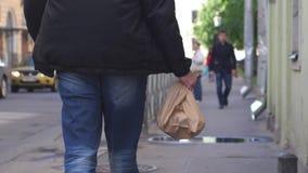 O homem de negócios novo mantém o saco disponivel e andando na cidade Vista traseira Fim acima 3840x1160, 4k filme