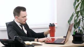 O homem de negócios novo no terno bebe do abanador dos esportes que senta-se em fps do escritório 60 video estoque