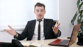 O homem de negócios novo no terno está sentando-se no escritório e é surpreendido 60 fps filme