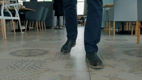 O homem de negócios novo no vestuário e em sapatas formais está andando ao longo da cafetaria vídeos de arquivo