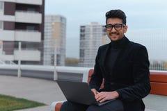 O homem de negócios novo nos monóculos trabalha no portátil que senta-se fora Foto de Stock Royalty Free