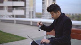 O homem de negócios novo nos monóculos trabalha no portátil que senta-se fora vídeos de arquivo