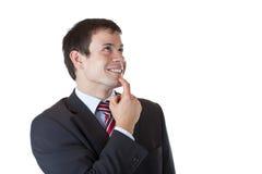O homem de negócios novo olha acima feliz e sorri Fotografia de Stock