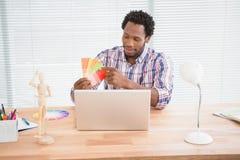 O homem de negócios novo olha cartões coloridos Fotografia de Stock