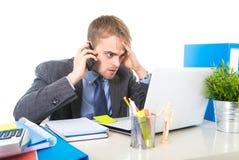 O homem de negócios novo preocupou a fala cansado no telefone celular no esforço do sofrimento do escritório Fotografia de Stock