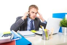 O homem de negócios novo preocupou a fala cansado no telefone celular no esforço do sofrimento do escritório Imagem de Stock